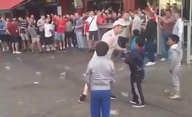 Frankreich: englischer Hooligan macht Drohgesten gegenüber bettelnden Romakindern; der Mob wirft Münzen und Kronkorken (Videostill)