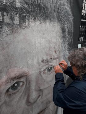 """""""Menschen kommen und nähen die Portraits zusammen. Sie bewachen bei strömendem Regen die Bilder der Ausstellung."""" (Foto: Klaus Schwertner/Twitter)"""